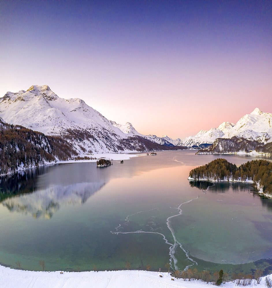 Pink sunrise on frozen Lake Sils and Piz Da La Margna covered with snow, Engadin, canton of Graubunden, Switzerland