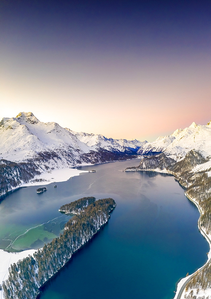 Snow capped Piz Da La Margna and Lake Sils at sunrise, aerial view, Engadin, canton of Graubunden, Switzerland (drone)