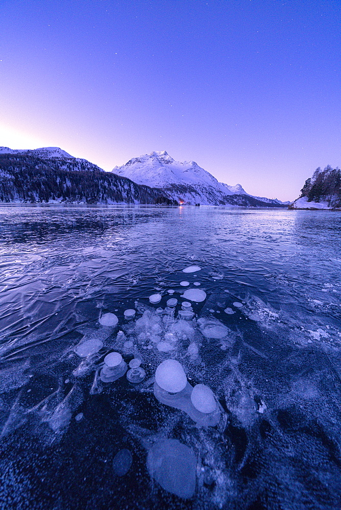Ice bubbles trapped in Lake Sils with Piz Da La Margna in background at dawn, Engadine, Graubunden canton, Switzerland, Europe - 1179-4707