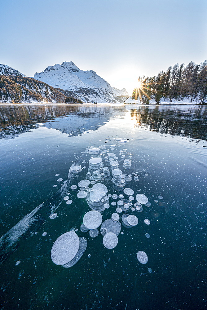 Ice bubbles trapped in frozen Lake Sils at sunset with Piz Da La Margna in background, Engadine, Graubunden canton, Switzerland, Europe - 1179-4711