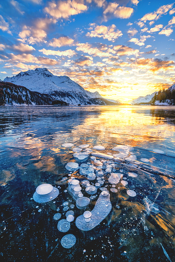 Clouds in the burning sky at sunset on Piz Da La Margna and ice bubbles trapped in Lake Sils, Engadine, Graubunden, Switzerland, Europe - 1179-4712