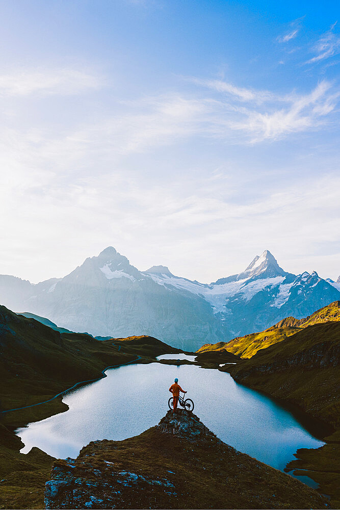 Mountain biker looking at Bachalpsee lake and Bernese Oberland mountains at dawn, Grindelwald, Bern Canton, Switzerland - 1179-5020