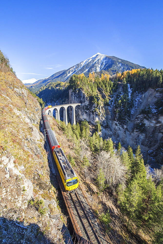 Bernina Express passes over the Landwasser Viadukt surrounded by colorful woods, Canton of Graubunden, Switzerland, Europe