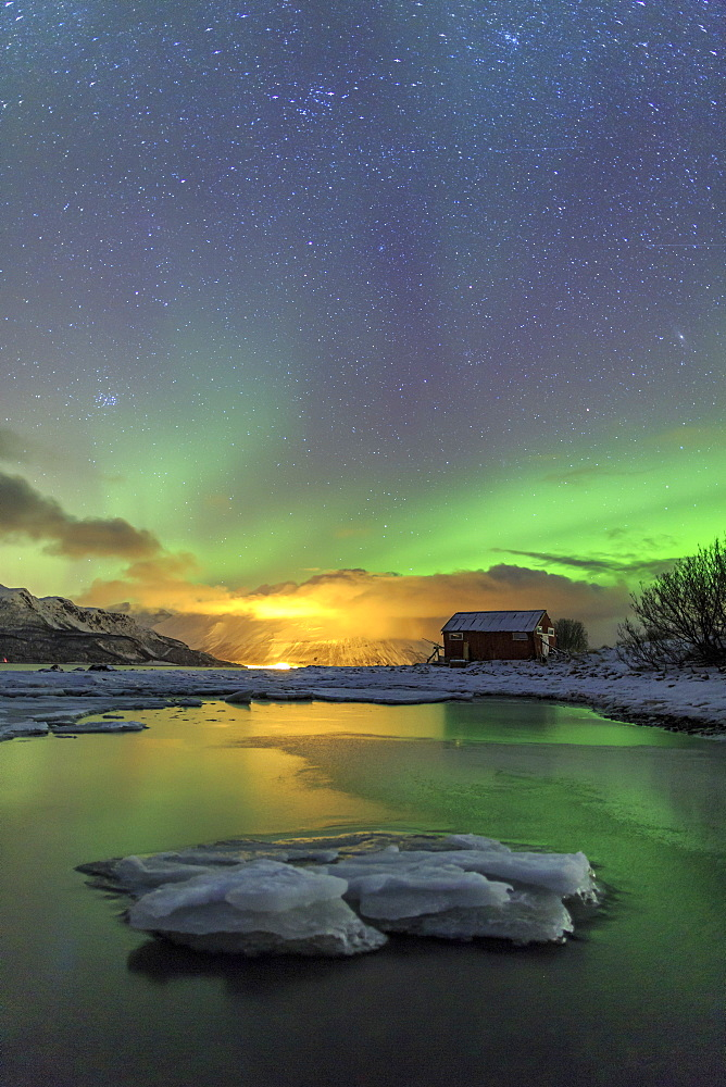 The Northern Lights illuminates the wooden cabin, Oteren, Storfjorden, Lyngen Alps, Troms, Lapland, Norway, Scandinavia, Europe