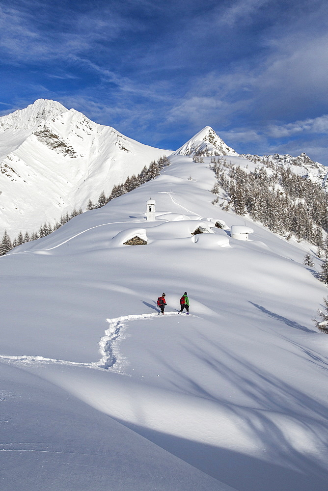 Hikers trying to approach the little village at the Scima Alp covered in snow, Valchiavenna, Lombardy, Italy, Europe