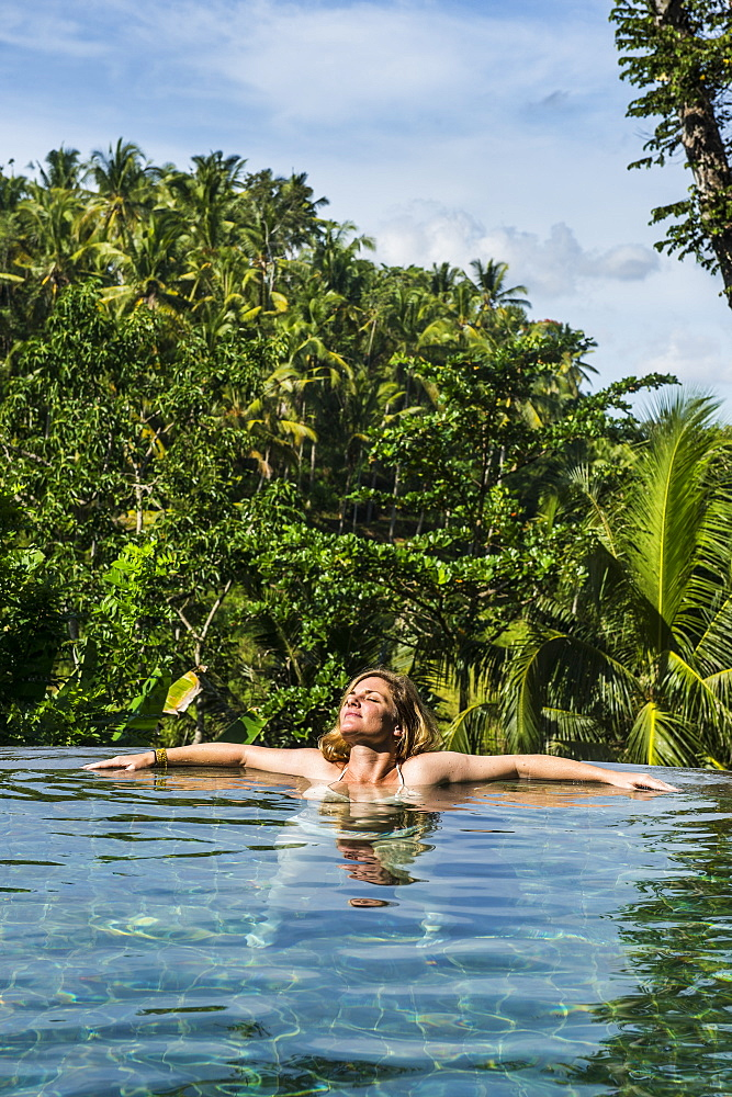 Woman enjoying an overflowing pool above a valley in the Kamandalu Ubud resort, Ubud, Bali, Indonesia, Southeast Asia, Asia