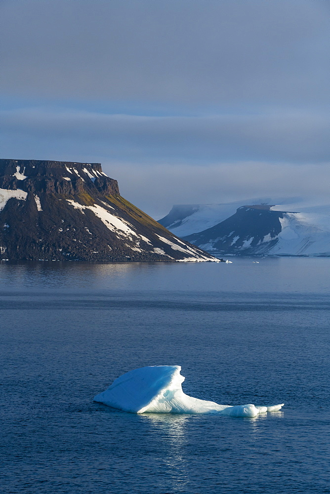 Iceberg floating in front of flat table mountains covered with ice, Franz Josef Land archipelago, Arkhangelsk Oblast, Arctic, Russia, Europe