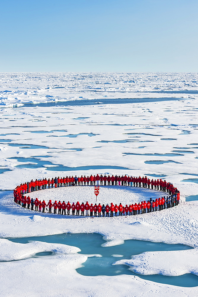 People wearing red forming circle around North Pole, Arctic