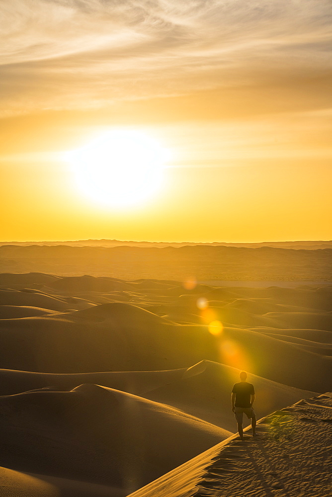 Man enjoying the sunset in the giant sand dunes of the Sahara Desert, Timimoun, western Algeria, North Africa, Africa