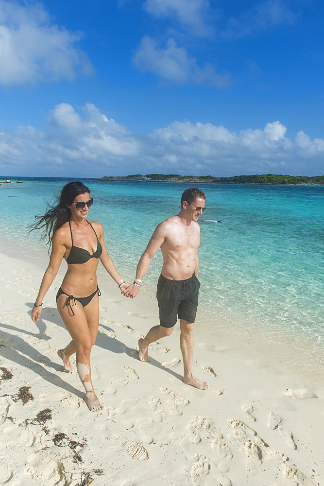 Couple walking on a white sand beach, Exumas, Bahamas, West Indies, Caribbean, Central America