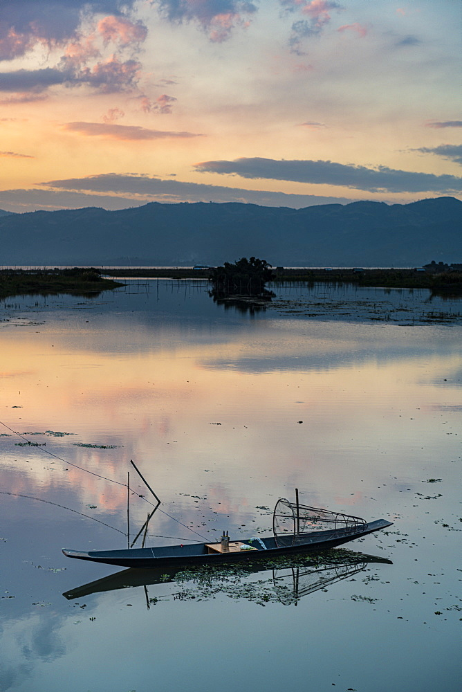 Clouds and traditional rowing boat reflecting in the water at sunset, Inle Lake, Shan state, Myanmar (Burma), Asia