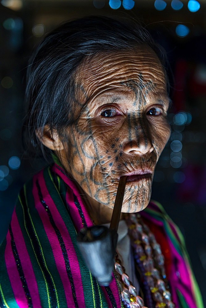 Chin woman with spiderweb tattoo smoking a pipe, Mindat, Chin state, Myanmar (Burma), Asia