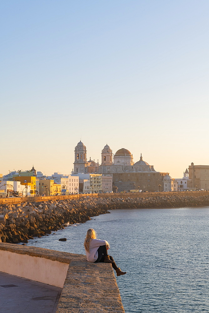 Woman enjoying the view of Santa Cruz Cathedral and ocean seen from the promenade along quayside, Cadiz, Andalusia, Spain