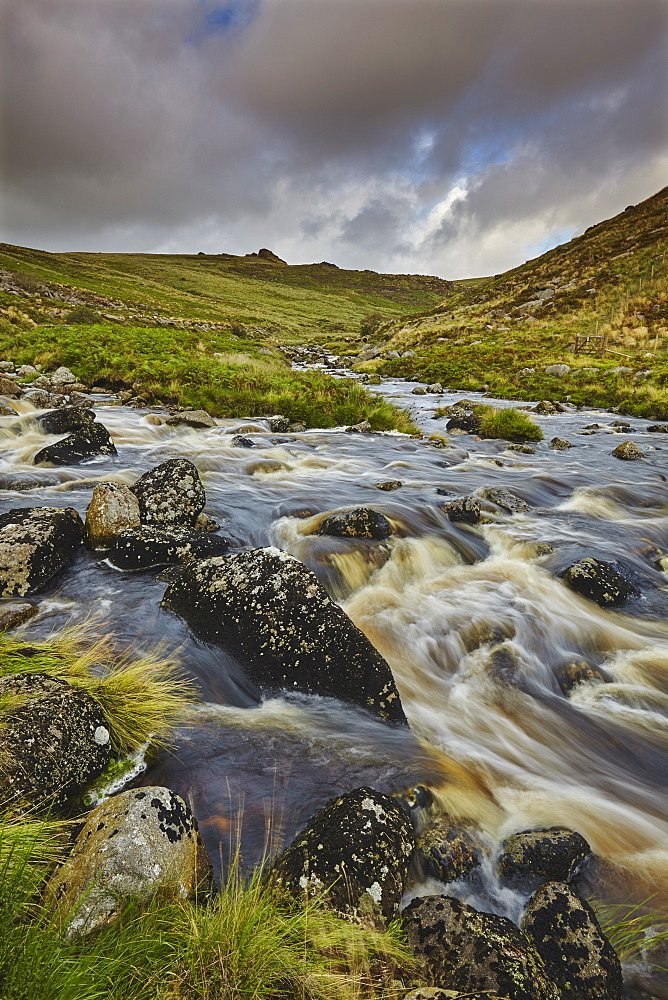 A moorland river rushes downill through a valley, en route from the moors to the sea, the River Tavy, in Dartmoor National Park, Devon, England, United Kingdom, Europe