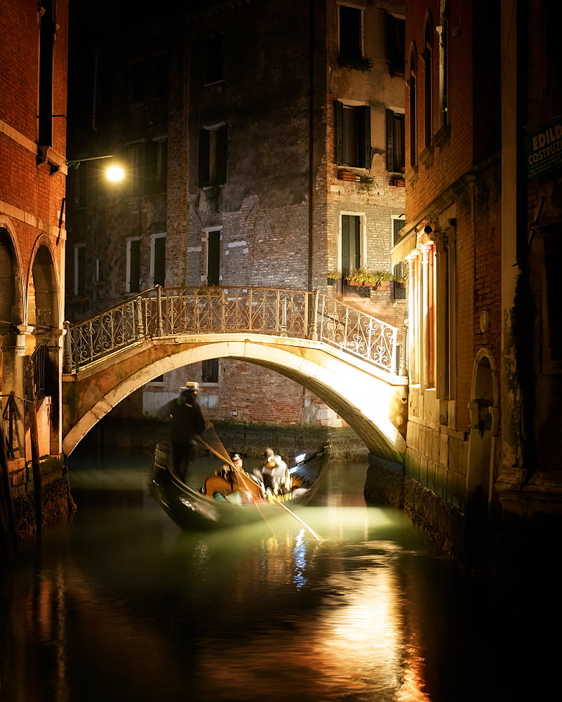Gondola under bridge at night in Venice, Italy, Europe