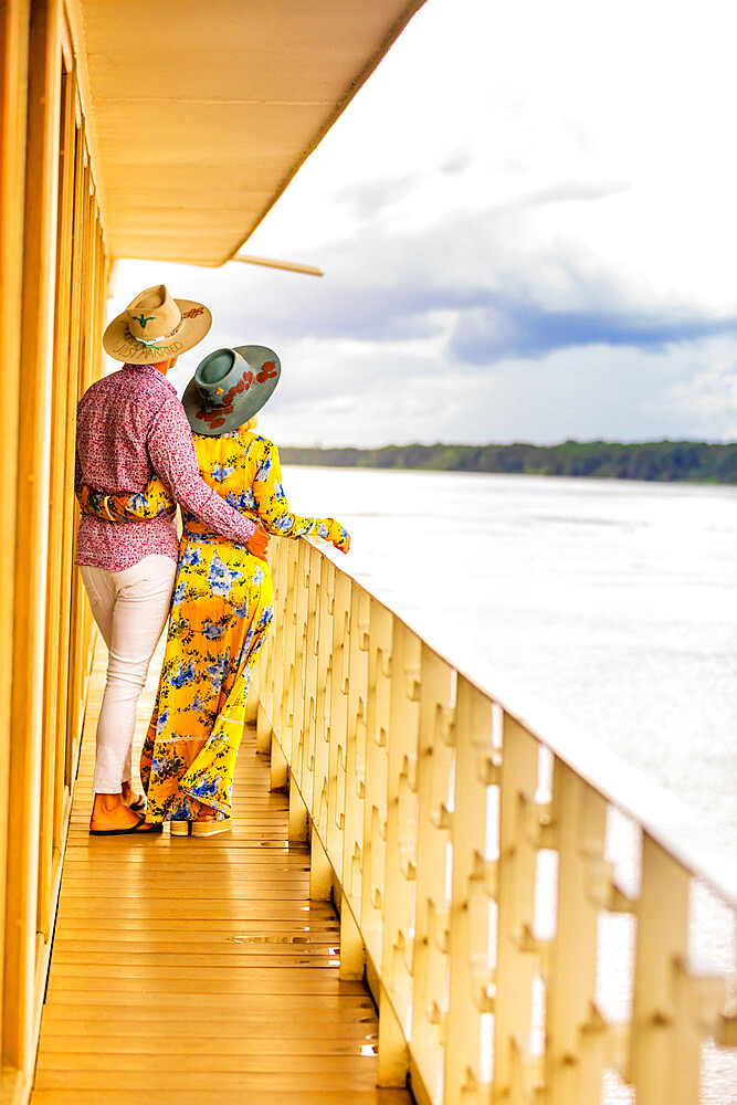Couple enjoying the view of the Amazon River aboard aboard a river boat.
