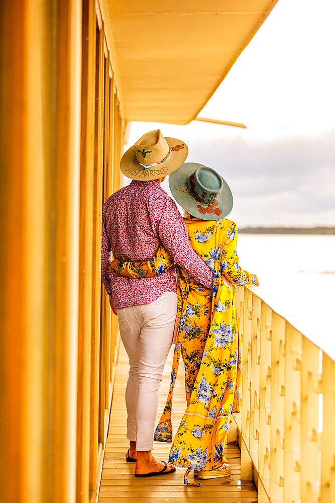 Couple enjoying the view of the Amazon River aboard a river boat.