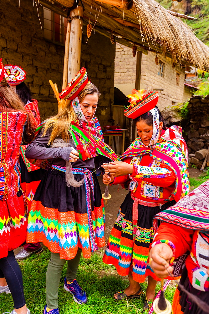 Visitors learning how to weave from the Huilloc weavers, Peru, South America