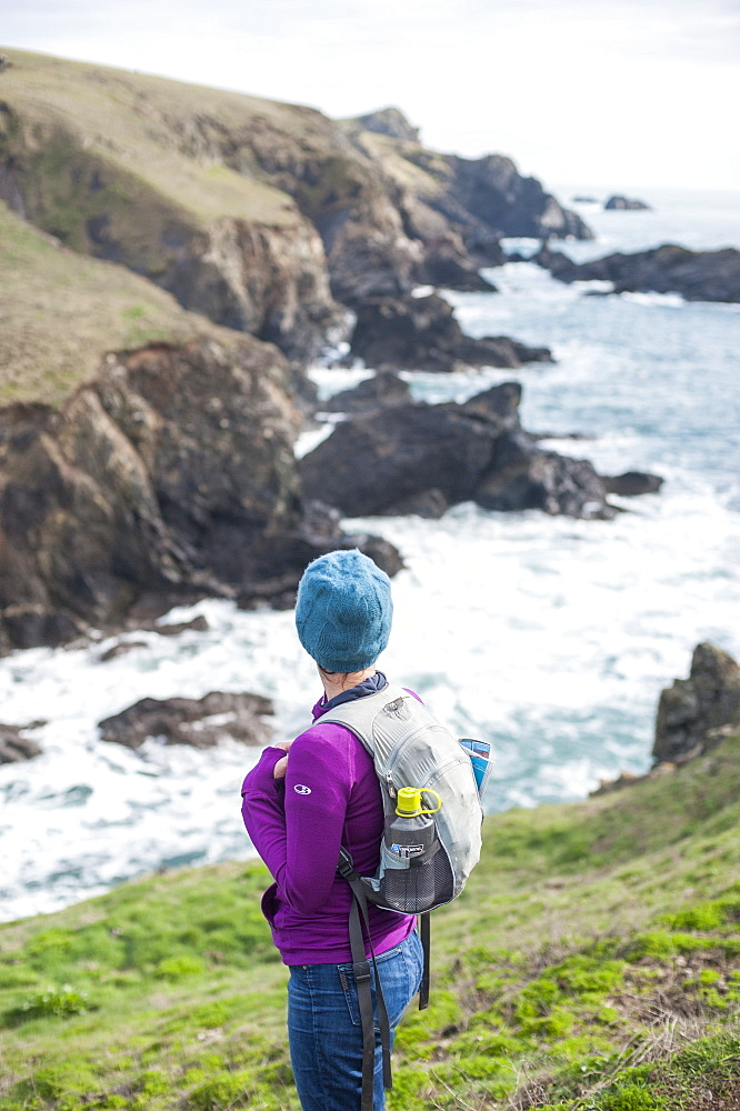 A woman hiking the coastal path on the west side of the The Lizard Penisuala in Cornwall in the United Kingdom