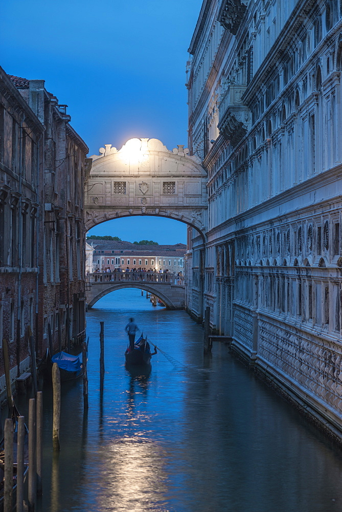 Gondolas pass under the Bridge of Sighs beside the Doges Palace in Venice at twilight, Venice, UNESCO World Heritage Site, Veneto, Italy, Europe