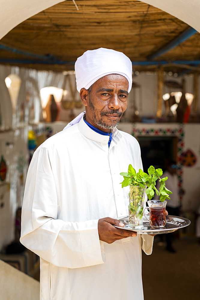 An Egyptian man holds a tray with a glass of mint tea and some fresh mint leaves, Aswan, Egypt, North Africa, Africa - 1225-1365