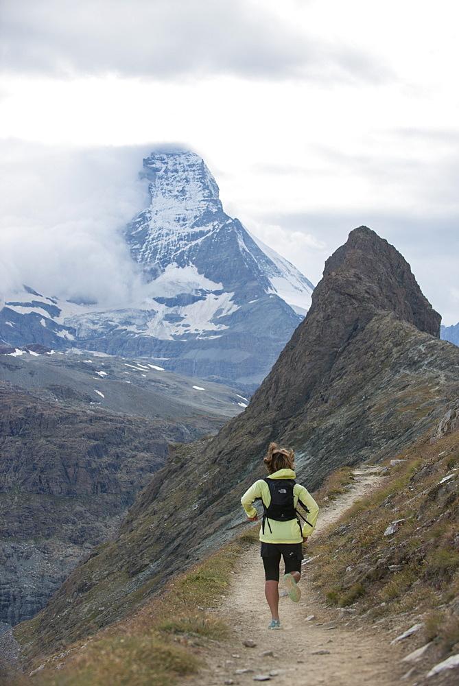 Running a trail in the Swiss Alps near Zermatt with a view of The Matterhorn in the distance, Zermatt, Valais, Switzerland, Europe