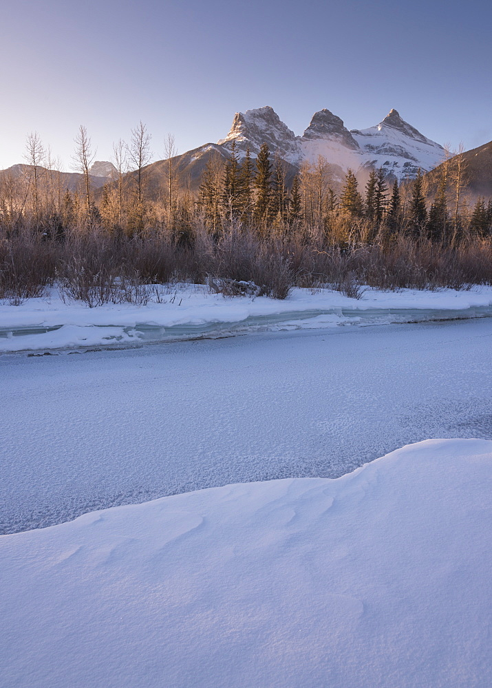 Winter sunrise with frozen Bow River and Three Sisters, Canmore, Alberta, Canadian Rockies