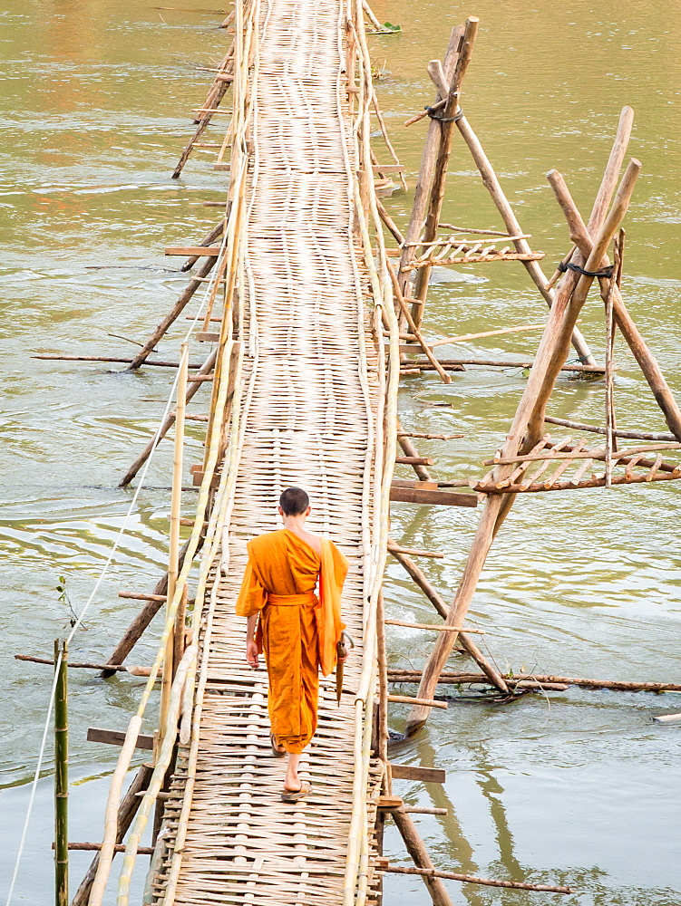Orange-clad Buddhist monk crossing a bamboo bridge, Luang Prabang, Laos, Indochina, Southeast Asia, Asia