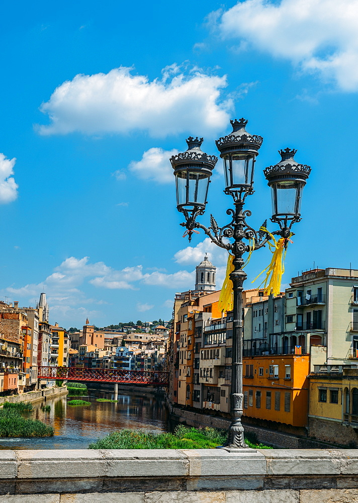 Colourful houses on the embankment of the River Onyard in historic centre and Eiffel Bridge in far background, Girona, Catalonia, Spain, Europe