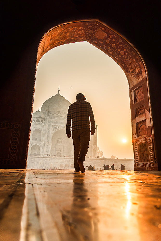 Sun rises behind the Taj Mahal as a man walks in, UNESCO World Heritage Site, Agra, Uttar Pradesh, India, Asia