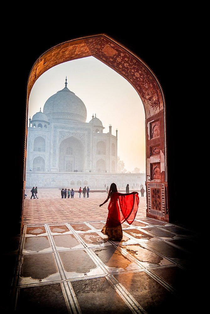 A lady twirls as the sun rises behind the Taj Mahal, UNESCO World Heritage Site, Agra, Uttar Pradesh, India, Asia