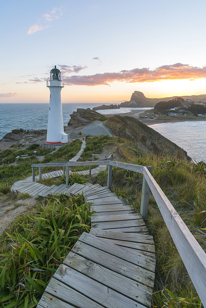Castlepoint lighthouse and Castle Rock at sunset. Castlepoint, Wairarapa region, North Island, New Zealand.