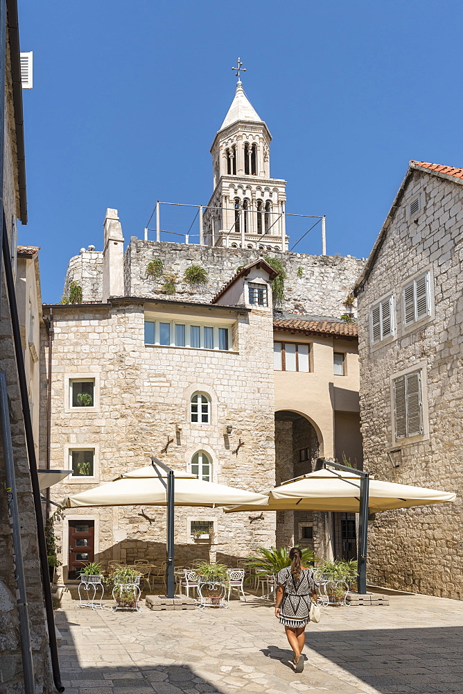 Woman walking in summer, with the bell tower of St. Domnius Cathedral in the background, Split, Split-Dalmatia county, Croatia, Europe - 1251-513