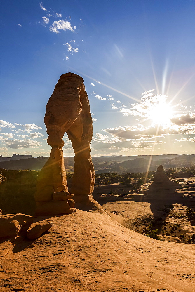 Delicate Arch with sun and clouds at golden hour. Arches National Park, Moab, Grand County, Utah, USA.