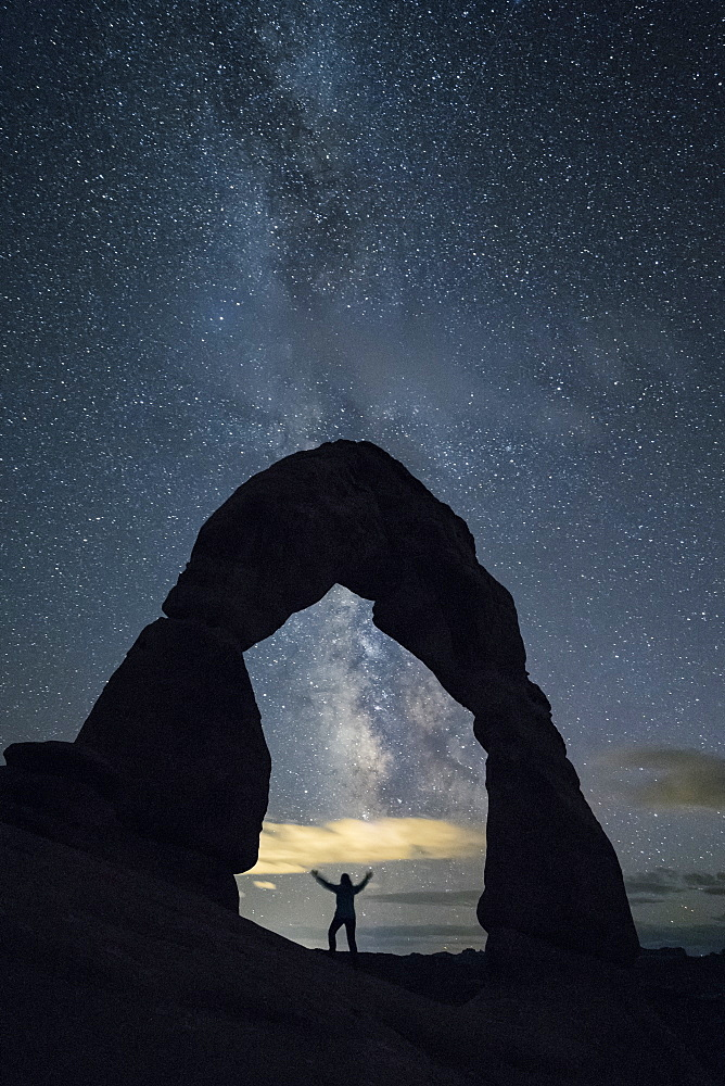 Milky Way and person under Delicate Arch. Arches National Park, Moab, Grand County, Utah, USA.