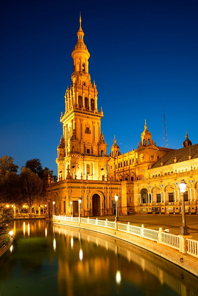 The North Tower of Plaza de España lit up at night, Parque de María Luisa, Seville, Andalusia, Spain,