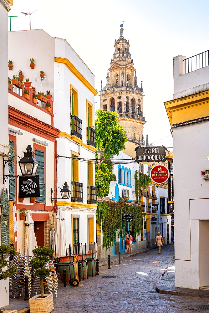 The Bell Tower of Cordoba Mosque Cathedral seen through a typical Andalusian street. Cordova, Andalusia, Spain.