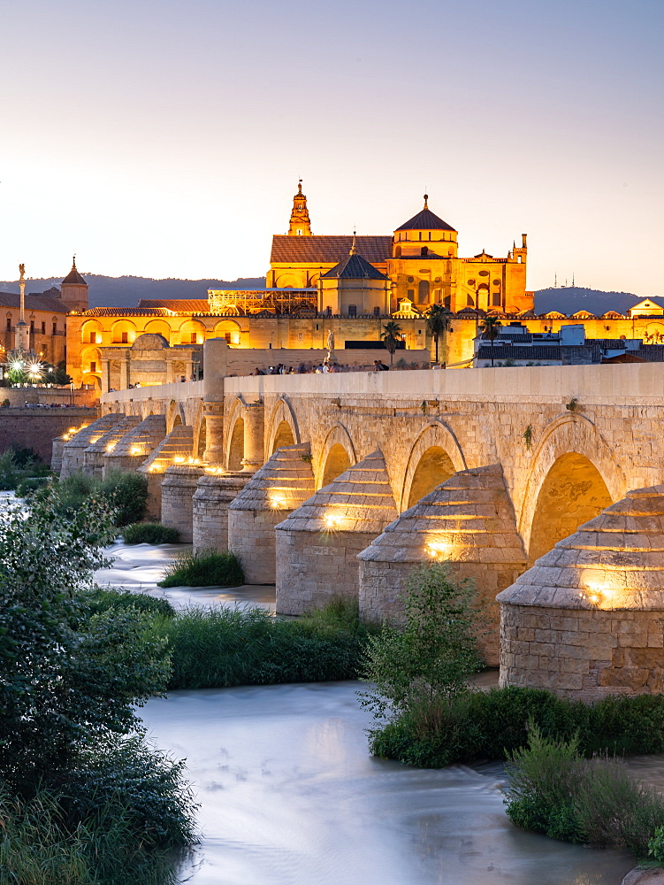 The Roman Bridge (Puente Romano) and The Great Mosque of Cordoba lit up during evening sunset. Andalusia. Spain