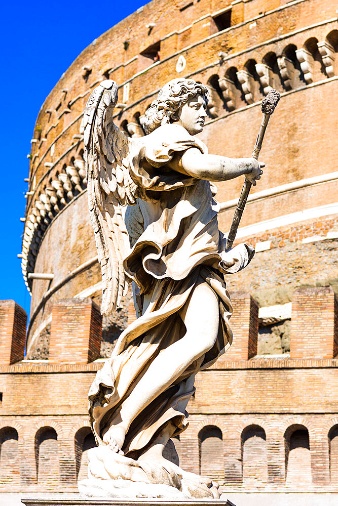 An angel statue from Ponte Sant'Angelo with Castle of the Holy Angel (Castel Sant'Angelo), Rome, Lazio, Italy, Europe
