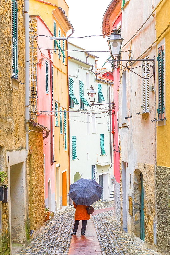 A person walks with an umbrella the main street of Civezza, Province of Imperia, Liguria, Italy, Europe.