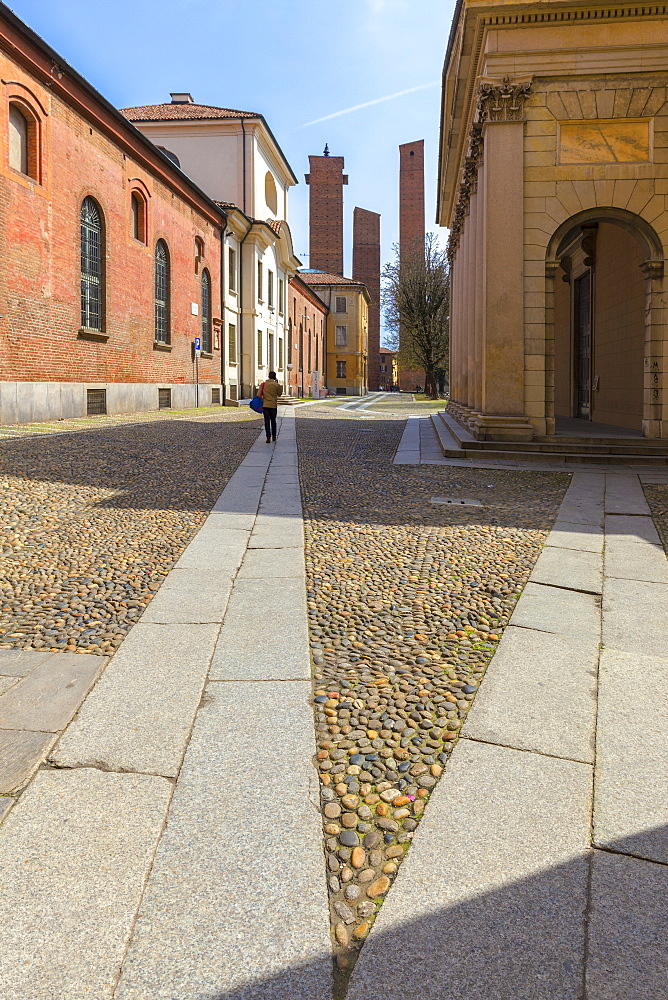 One person walks in a street with medieval towers in the background, Pavia, Pavia province, Lombardy, Italy, Europe - 1269-180