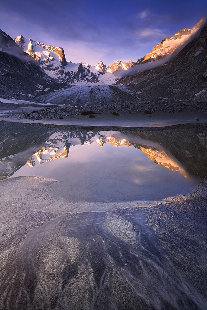 Sunrise from a pond at Forno Glacier, Forno Valley, Maloja Pass, Engadin, Graubünden, Switzerland, Europe.