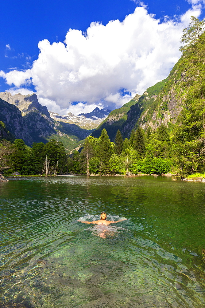 A girl swims in a clear alpine lake, Val di Mello (Mello Valley), Valmasino, Valtellina, Lombardy, Italy, Europe - 1269-225