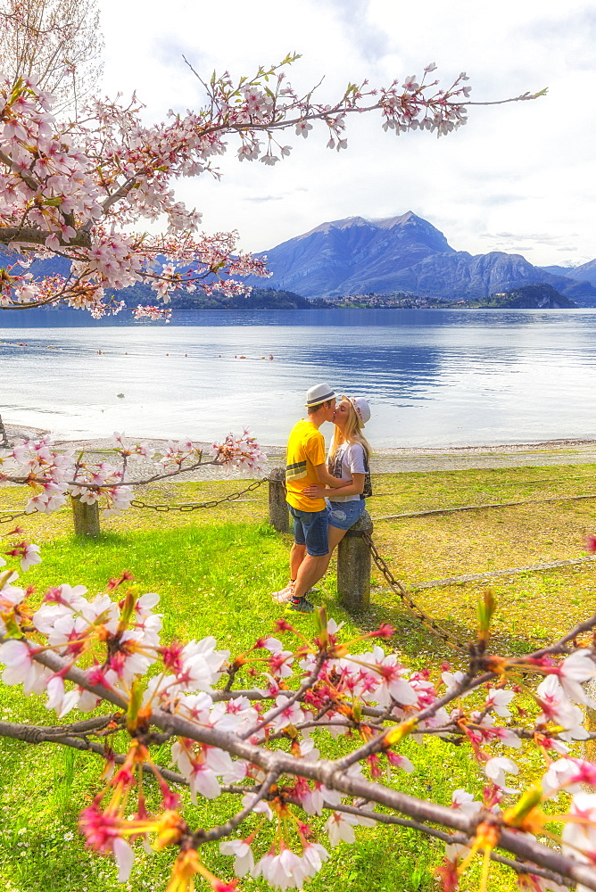 Couple of tourists kiss in front of the lake. Lierna, Province of Lecco, Como Lake, Lombardy, Italy, Europe. - 1269-249