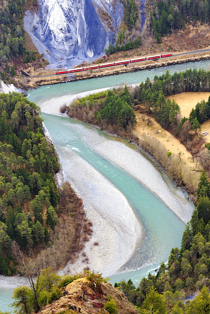 The red train travels along the Rhine River. Rhein Gorge(Ruinaulta), Flims, Imboden, Graubunden, Switzerland, Europe
