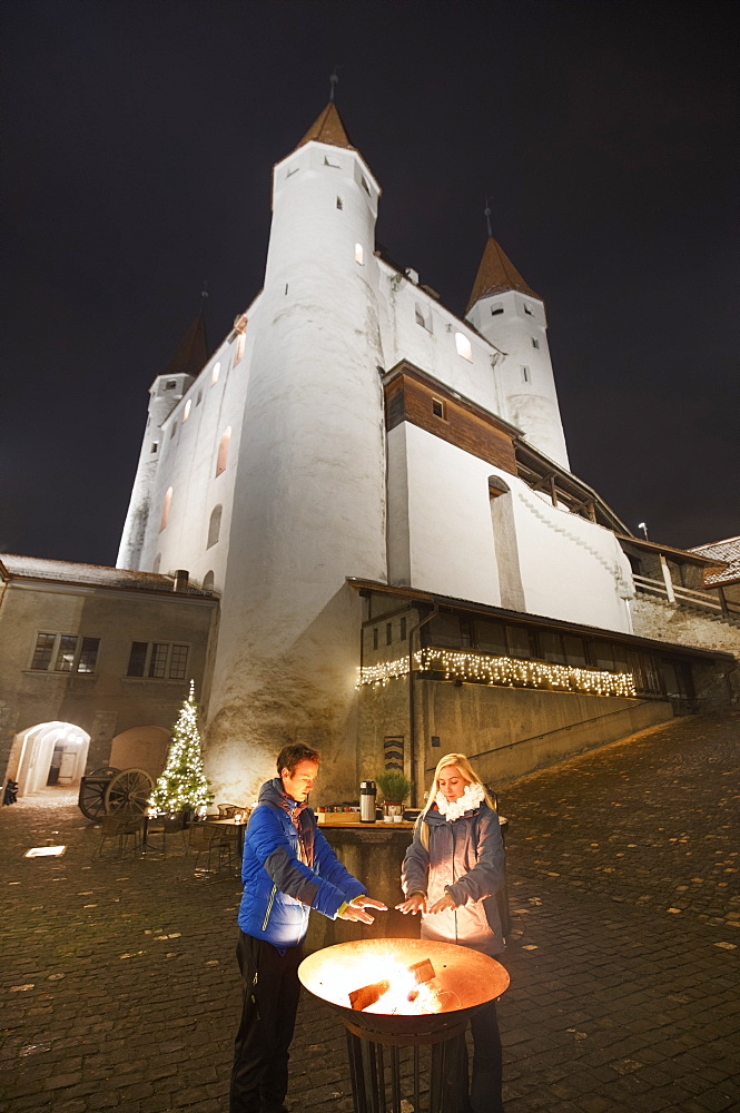 A couple of people warm their hands with the castle in the backgound. Thun, Canton of Bern, Switzerland, Europe.