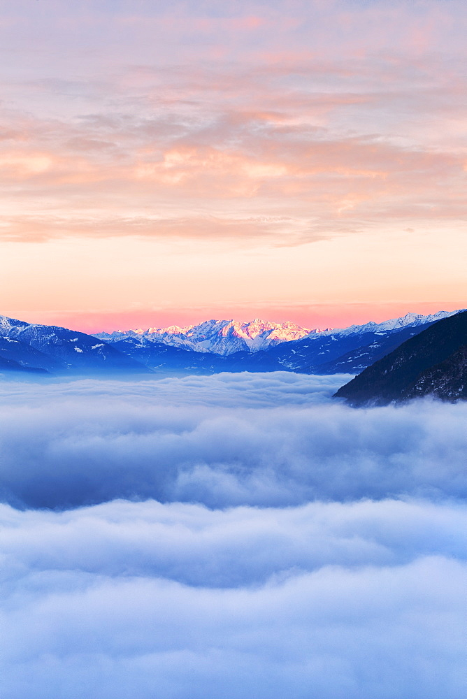 Sea of fog in Valtellina with Adamello group in the background at sunset. Valtellina, Lombardy, Italy, Europe.