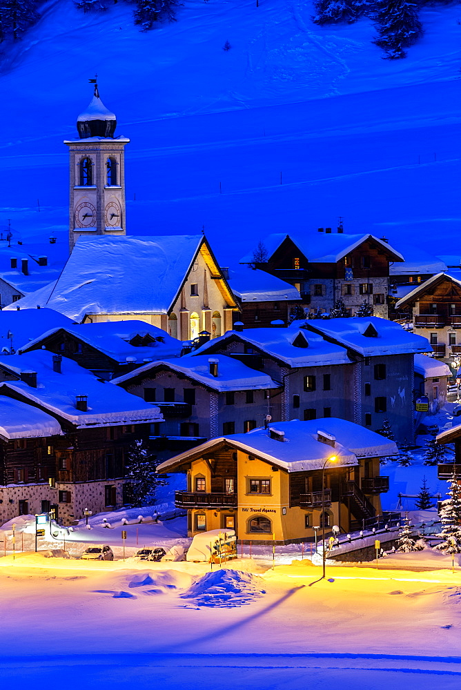 Church and houses illuminated during a winter twilight, Livigno, Valtellina, Lombardy, Italy, Europe - 1269-457