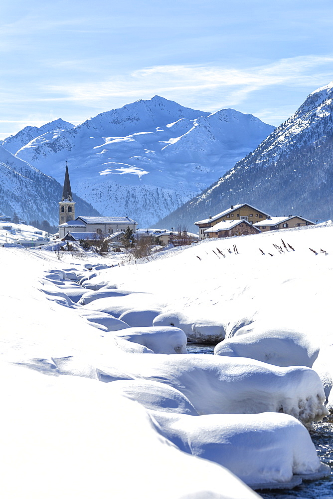 Torrent with church in winter snow, Livigno, Valtellina, Lombardy, Italy, Europe