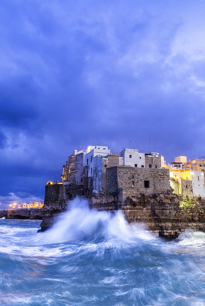 Waves crash on the cliff during a winter storm at dusk, Polignano a Mare, Apulia, Italy, Europe